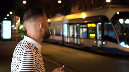 alışkanlık : Bearded man in striped polo t shirt smoke electronic cigarette iqos at night on street with cars on background Stok Video