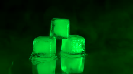 ice cube : Close up shot three ice cubes lie on a mirrored table with green light on it
