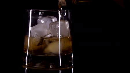 бурбон : whiskey is poured into a glass with ice on a black background Стоковые видеозаписи