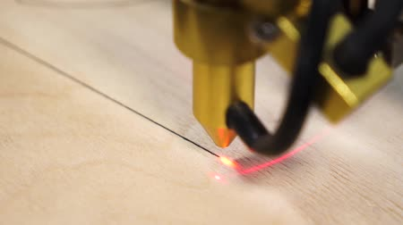 Machine for laser cutting wood close up cuts board and make straight line.
