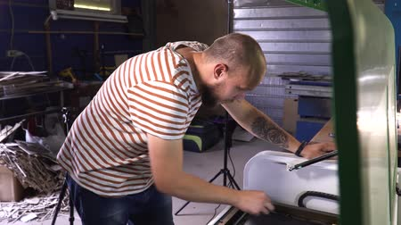 A man in striped T-shirt working on cutting wood machine. man is bold with beard