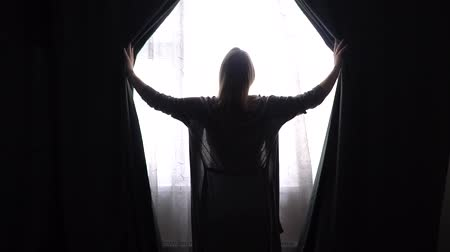 unveil : girl or woman in gray bathrobe at home open curtains and look into window.