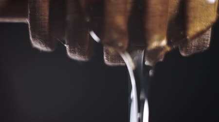thick : Honey falls from special honey spoon or honey dipper on black bachground Stock Footage