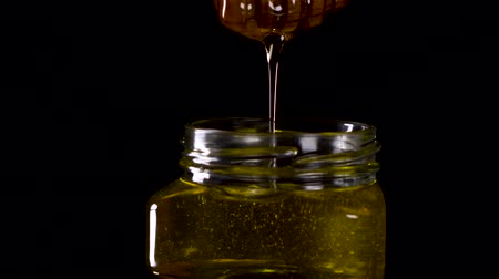 sirup : Close up tasty honey dripping from honey dipper in a jar. Tasty footage