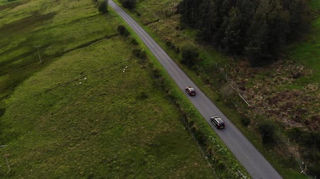 camera move : Two SUVs drive one after another along country road in field. Aerial view. Stock Footage