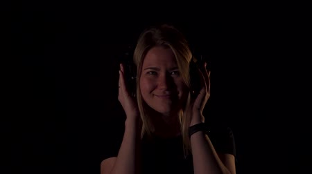 contornos : Portrait of nice blonde girl or woman on black background in black t shirt. Listen music in wireless headphones and very happy