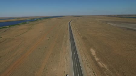 運転 : Aerial view on empty road in the desert or field in the middle of nowhere. Cinematic footage of 2 lanes motorway. 動画素材