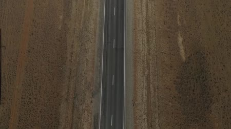 bird's eye view : Aerial view on empty road in the desert or field in the middle of nowhere. Cinematic footage of 2 lanes motorway. Stock Footage