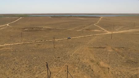 wasteland : Side aerial view of a silver ride in the steppe or in the field in the middle of nowhere. Stock Footage