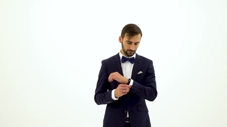 beyaz yakalı işçi : Slow motion portrait of young bussinesman with beard in costume with bowtie adjusting suit jacket sleeves