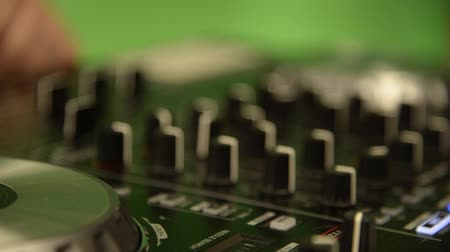 behind bars : DJ stands behind the mixer, DJ controller, mixes music, twists the levers, shooting hands close-up