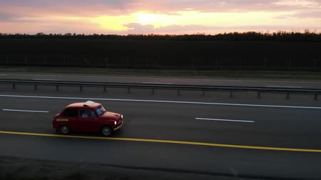 沿岸の : Great aerial footage of red small retro car drive on 4 lane motorway in sunset or sunrise with turned headlights. Side close up shot