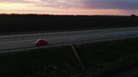 沿岸の : Great aerial footage of red small retro car drive on 4 lane motorway in sunset or sunrise with turned headlights