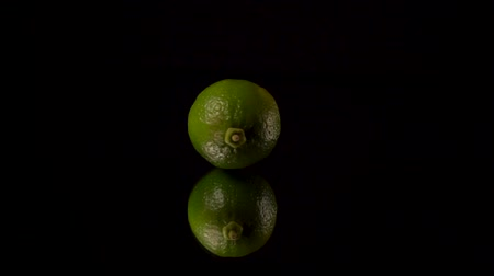 limonada : Green fresh lime or green lemon spins on black background on mirror.