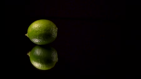 celý : Green fresh lime or green lemon roll on black background on mirror.