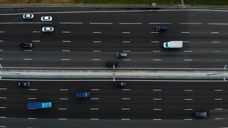 cauda : Aerial view of a motorway. Camera move slow left. A lot of cars ride on the 10 lanes motorway.
