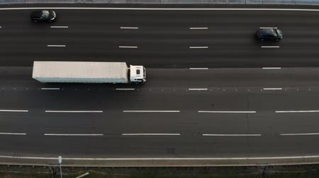 способ : Seven lane motorway aerial view with a lot of trucks and cars passing by and drive to the place.