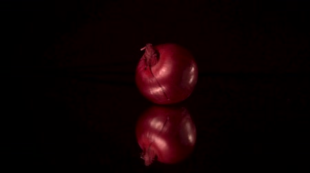 pivoting : Fresh red onion spin on the mirror or mirrored black table with black background.