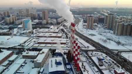clean electricity production : Aerial view of industrial zone with large red and white pipes with white smoke. Smoke is poured from the factory pipe in contrast to the sun. Pollution of the environment: pipes with smoke.