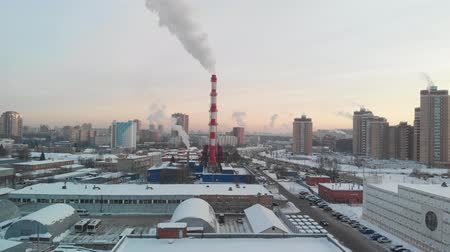 work at height : Aerial view of industrial zone with large red and white pipes with white smoke. Smoke is poured from the factory pipe in contrast to the sun. Pollution of the environment: pipes with smoke.