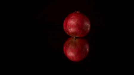 гранат : Fresh red pomegranate rotating and rolling on a black mirror table. Black background. Стоковые видеозаписи