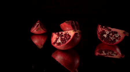 皮が付いたままの : Fresh red pomegranate split into parts. slow motion. Black background. Fall into pieces 動画素材