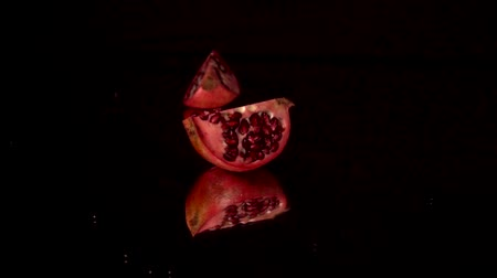 unpeeled : one slice of fresh red pomegranate rotating on a black mirror table. Black background Stock Footage