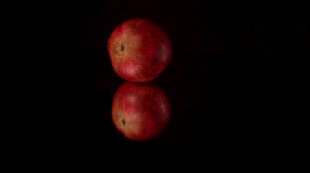 ve slupce : Fresh red pomegranate rotating and rolling on a black mirror table. Black background