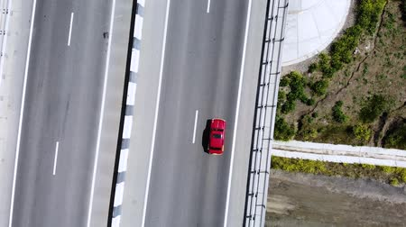 pairar : Aerial view of a red retro car drive on road or highway in the middle of the day. Not a lot of cars on motorway.