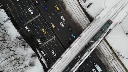 establishing shot : Aerial top down view of traffic jam on a road with moving train on the bridge. Winter time. Stock Footage