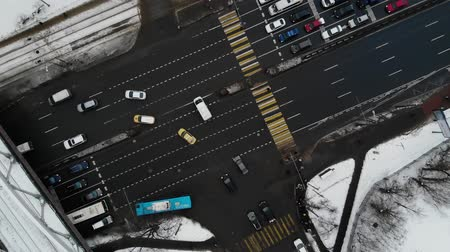 establishing shot : Aerial view of road with cars and buses. traffic in winter time with railway bridge. Spin around road junction.