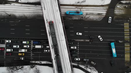 csomópont : Aerial top down view of traffic jam on a winter road with a lot of cars and busses, blue tram and gray train on railroad