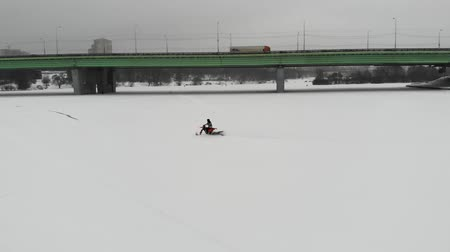 going round : Aerial view of riding on snowmobile on the frozen river. Drive snow truck on a white snow.