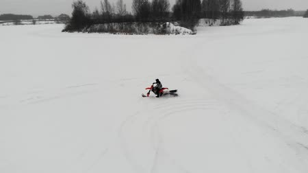 arktický : Aerial view of riding on snowmobile on the frozen river. Drive snow truck on a white snow.