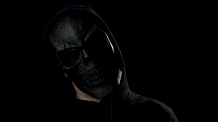 szkielet : Portrait of spooky man in black skull mask looking in camera and scary you