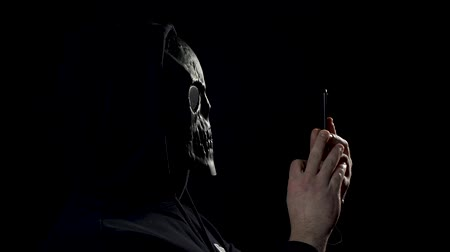 invisible : Man in a black room in skull mask. Scary man in mask using smartphone