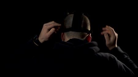 stalker : Man in black hoody in a black room in skull mask. Man put a mask, turn around and look into camera Stock Footage