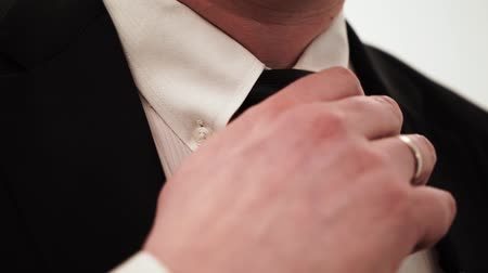 getting ready : Bussinesman in black suit with white shirt and tie adjusting tie.