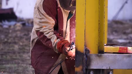 skillful : Man in red and gray robe welding yellow metal construction in safety gloves and safety mask. Safety first.