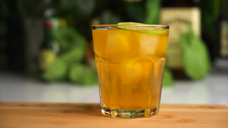 tonik : Slow motion of slices of lime fall into orange soda in glass with ice