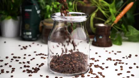 арабика : Slow motion empty transparent jar filled with coffee beans on white table with coffee beans lay on table. Стоковые видеозаписи