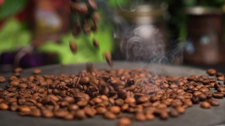 roaster : Slow motion coffee beans are roasted on a frying pan, smoke comes from coffee beans. Nice background with green plants and coffee pack. Falling coffee beans. Stock Footage