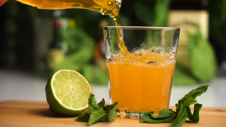 Orange soda slow motion fill glass with ice. soda drink. Glass stand on wooden plate with lime and mint on it. Stock mozgókép