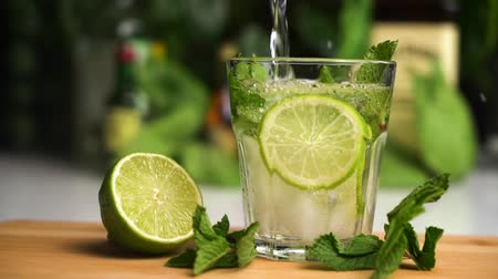 hilton : soda slow motion fill glass with ice. soda drink. Glass stand on wooden plate with lime and mint on it.
