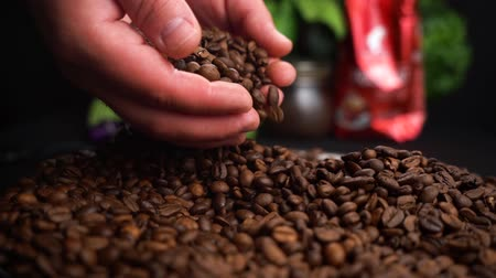 Roasted Coffee Beans Falls Down from Farmer Hands on a black table with food background