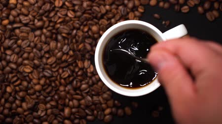 Top view of person hand stirring coffee in white cup with spoon on black table with coffee beans on table. Stock mozgókép