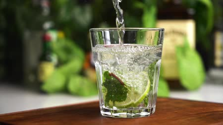 Slow motion mineral water or soda fill glass with lime, mint and ice cubes. Food background. Stock mozgókép