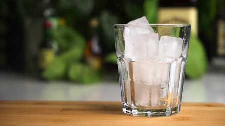 Slow motion of ice cubes fall into a glass stand on wooden desk. Cocktail concept.