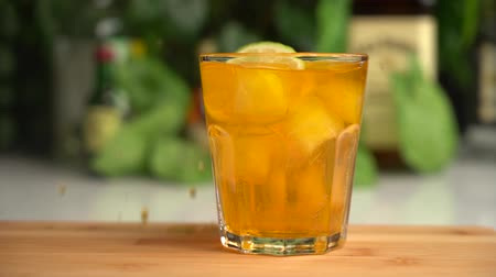 Slow motion of slices of lime fall into orange soda in glass with ice