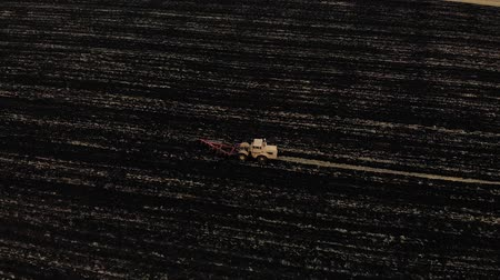 Tractor plowing fields, preparing land for sowing. Aerial view. Farmer in tractor preparing land in farmlands. Tractor plows a field. Agriculture industry. Black field and white tractor.